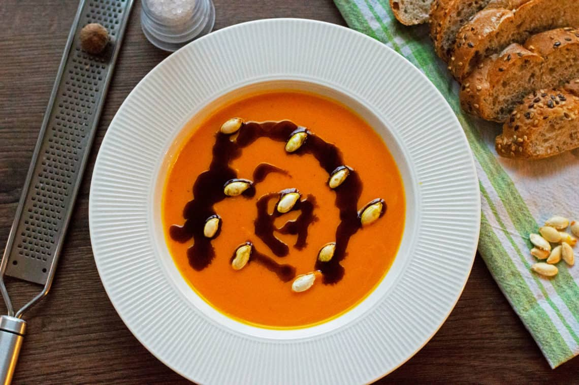 A top shot photo of Pumpkin Soup with nutmeg, pumpkin oil and pumpkin seeds served with some wholegrain bread