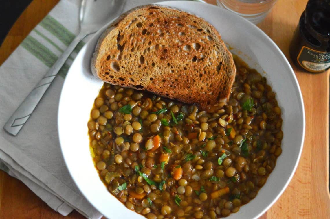 puy lentil soup in a white bowl with a piece of toast
