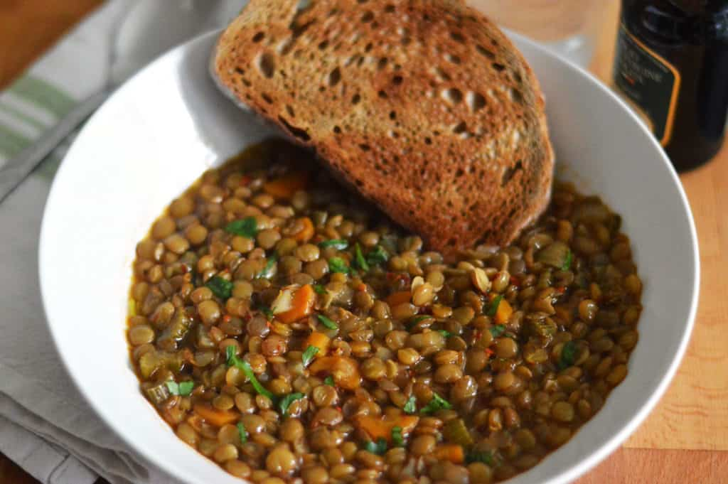 Side shot photo of puy lentil soup in a white bowl