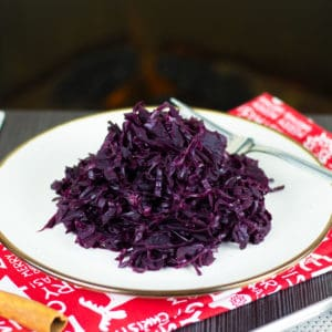 A picture of my Braised Red Cabbage recipe surrounded by spices in front of a fireplace
