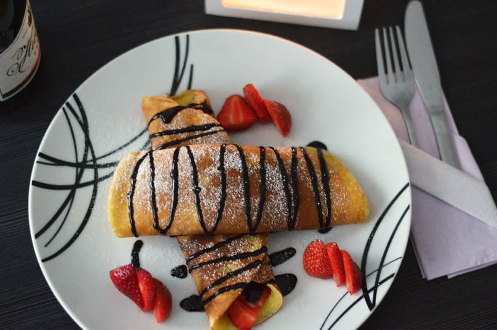 A top shot of my French Crepes recipe in a dim candle light setting