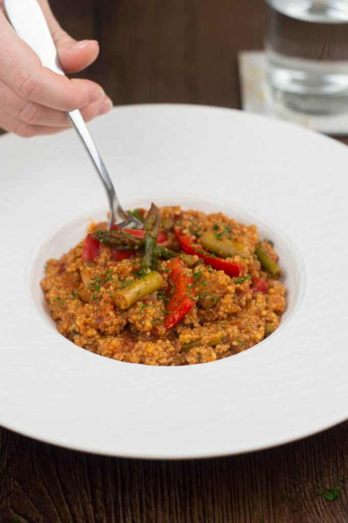 A fork digging into a bowl of moroccan couscous