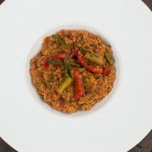 A overhead photo of Moroccan couscous in a fancy white bowl