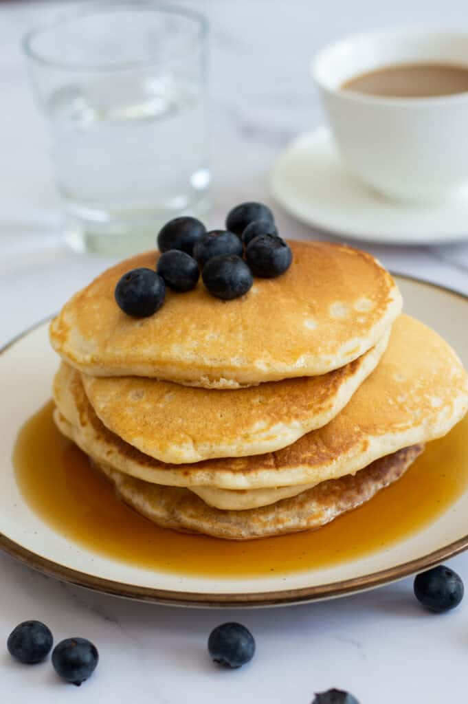 American style pancakes topped with blueberries and maple syrup
