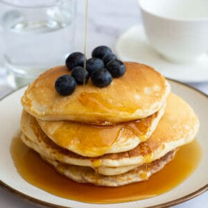American Pancakes with blueberries with maple syrup being drizzled on top