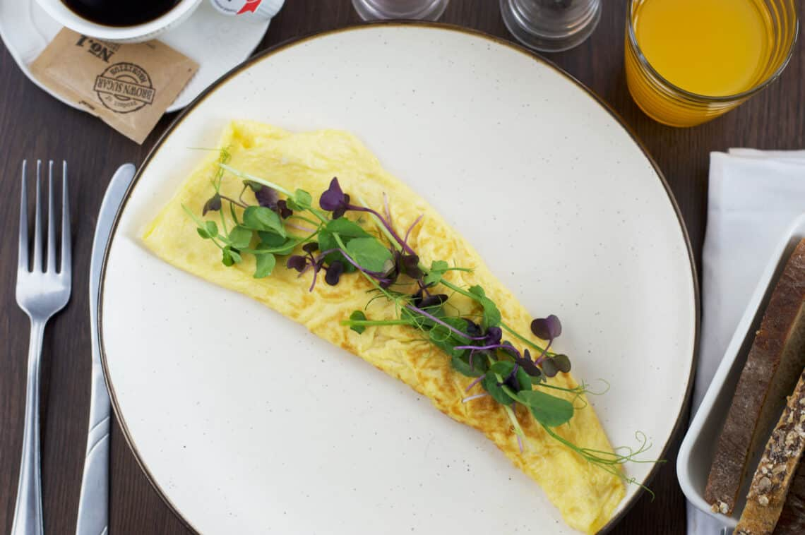 Omelette on a plate served with toast, coffee & orange juice
