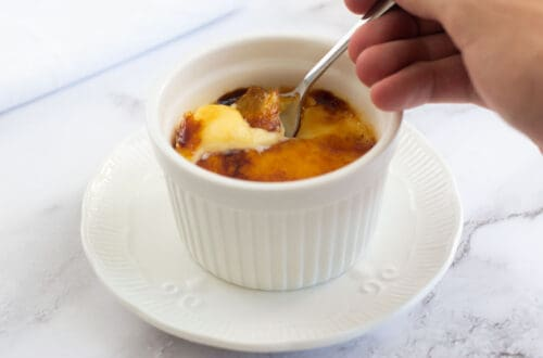 Breaking the caramel with a teaspoon on the creme brûlée