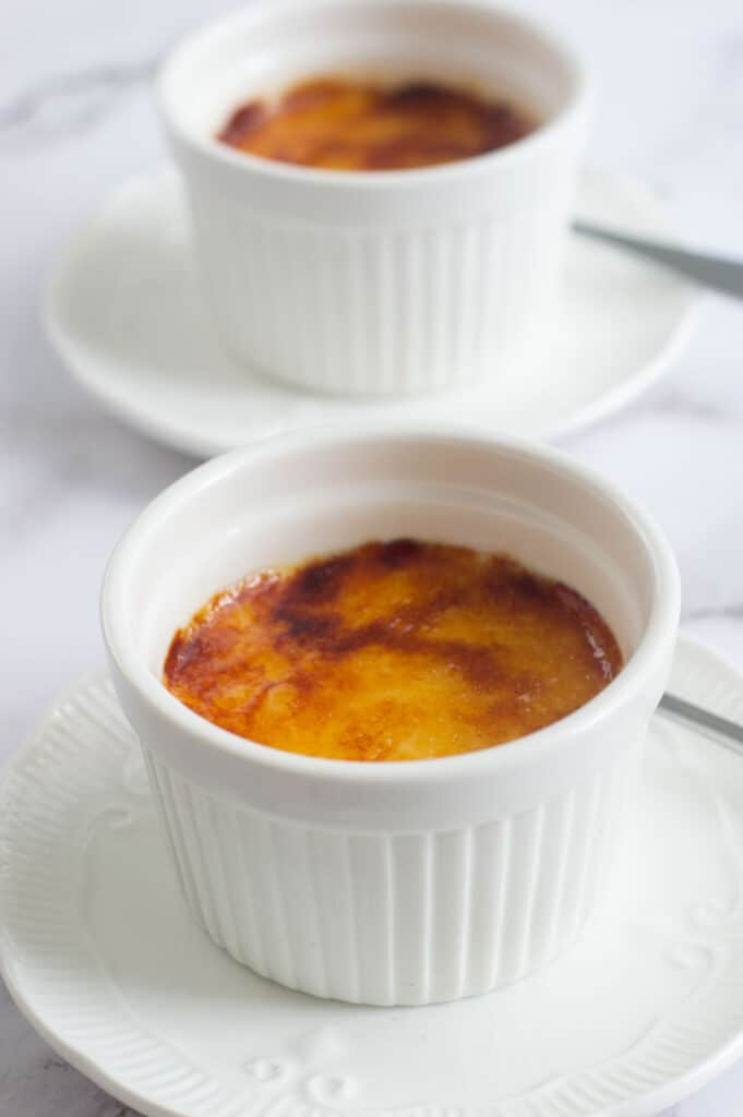 Two creme brulees in white ramekins on white plates