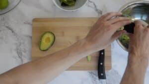 Squeezing a avocado into a mixing bowl