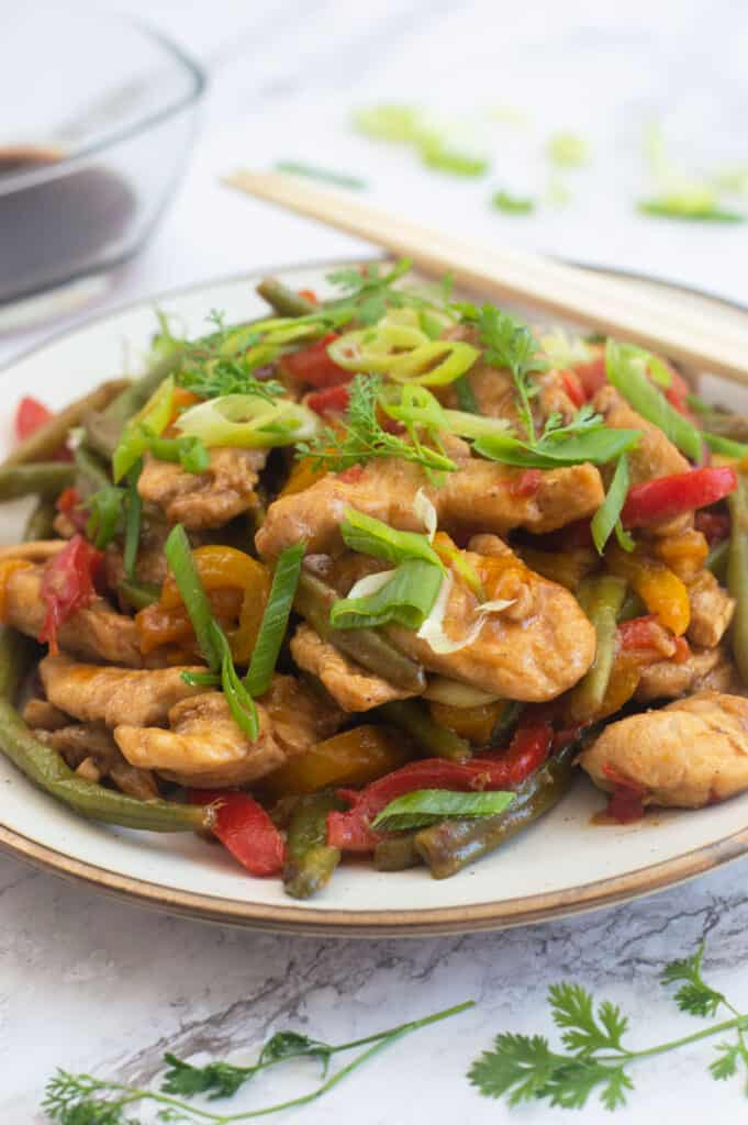 Chicken stir fry with lots of vegetables on a plate with chop sticks
