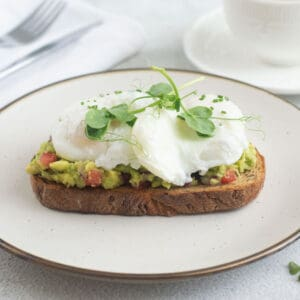 Poached eggs on toast with smacked avocado garnished with chives and pea shoots