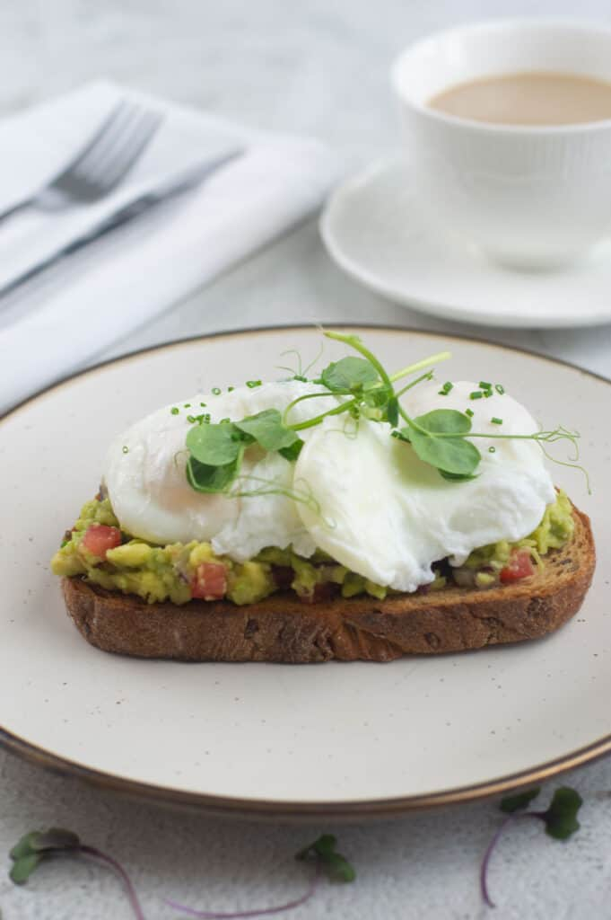 Poached eggs with smashed avocado on toast with coffee
