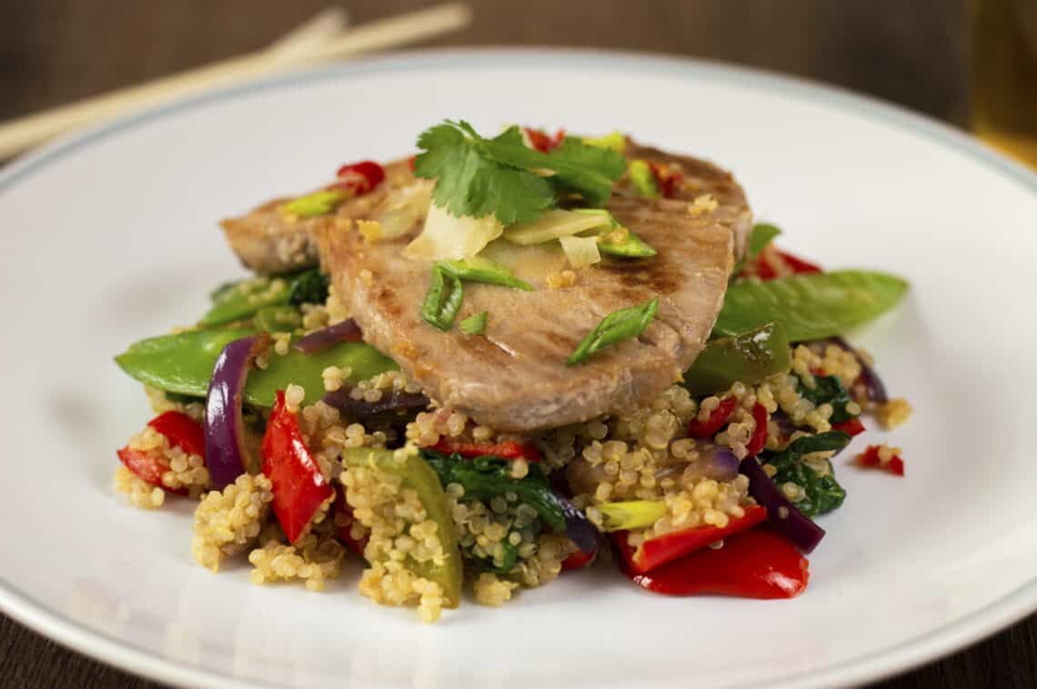 A plate of Seared Tuna steak on a pile of quinoa and stir-fried vegetables