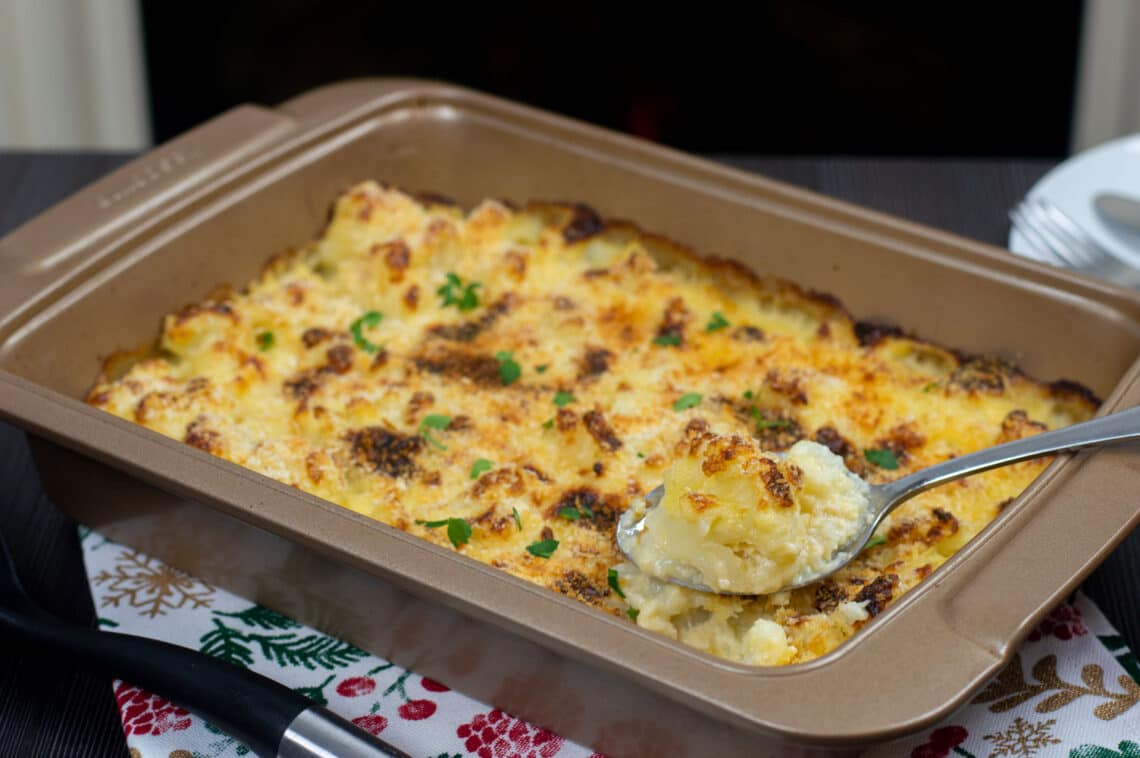 A baking tray with freshly baked cauliflower cheese with a crunchy topping. A spoon taking out a piece of cauliflower from the baking tray.