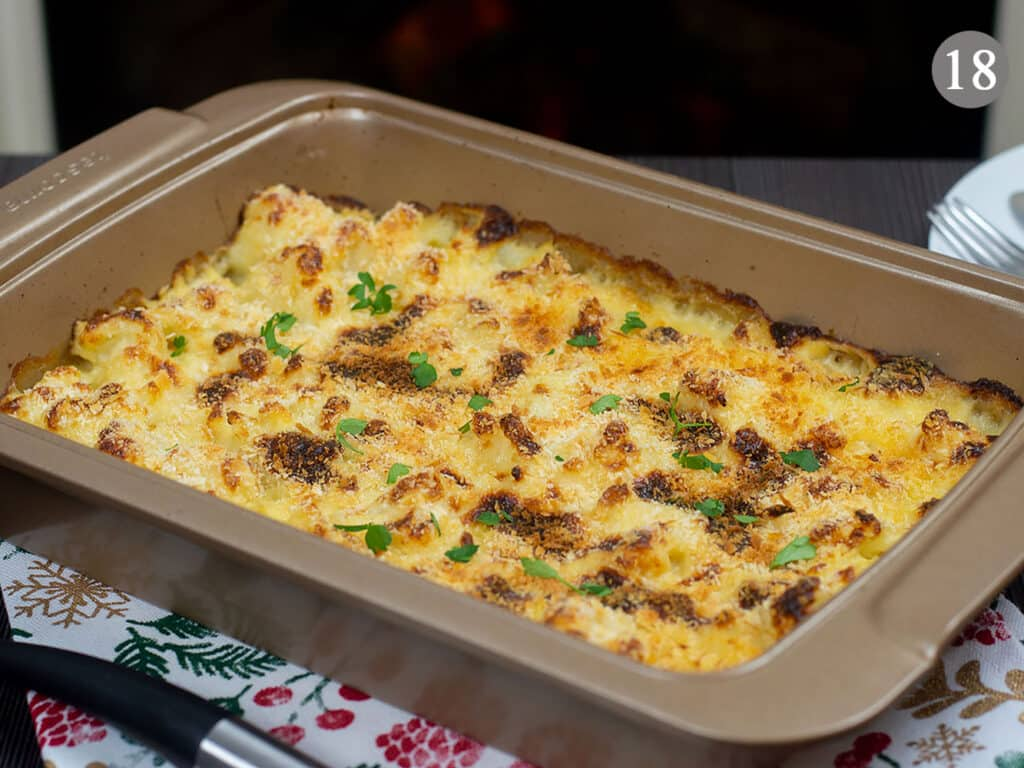 A baking tray with freshly baked cauliflower cheese on a table, with a fireplace in the background.