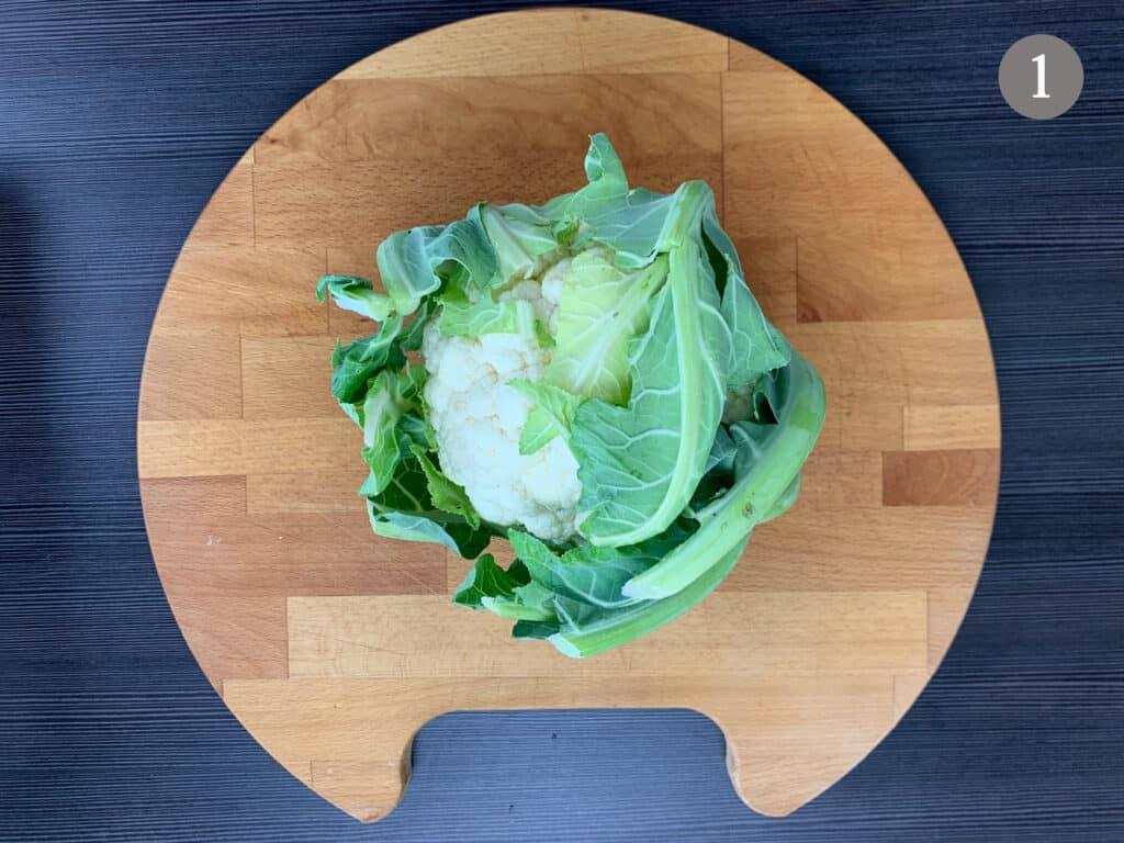 A non prepped cauliflower on a chopping board