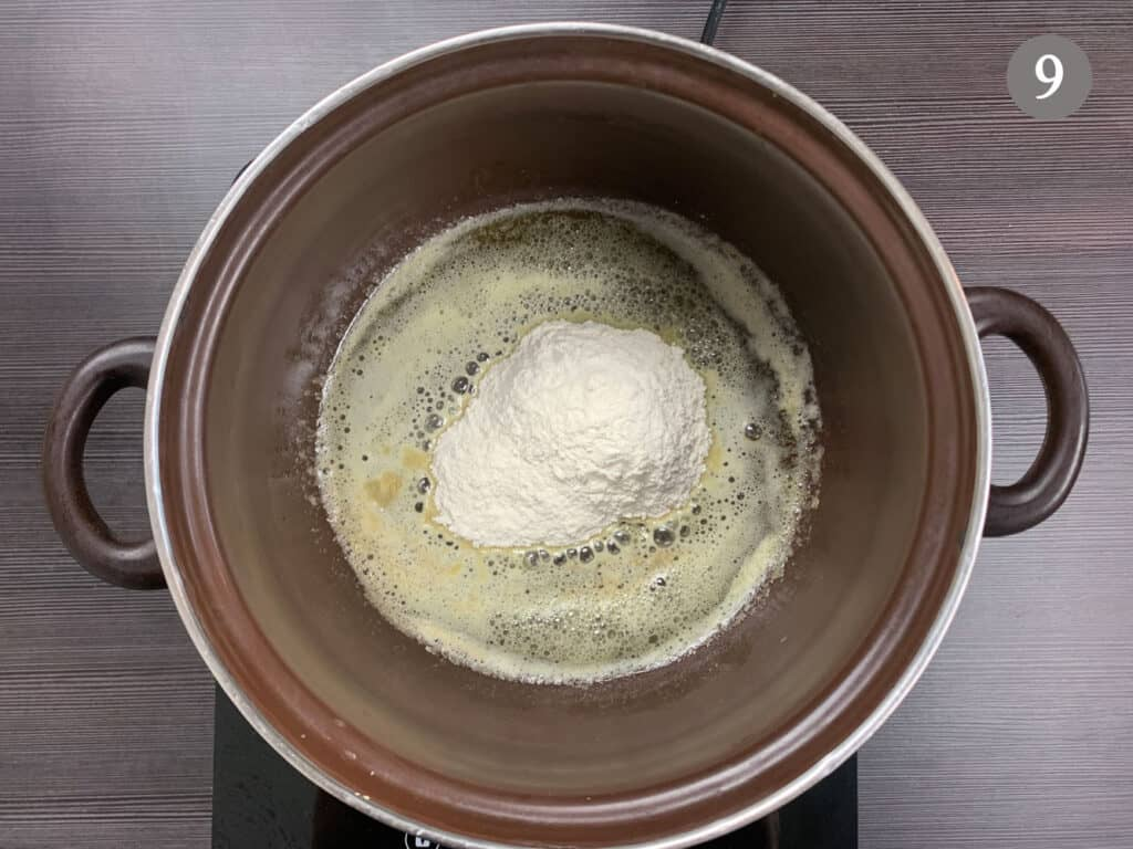 Adding flour to a pot of melted butter