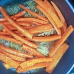 Carrots glazing in a pan with butter and brown sugar