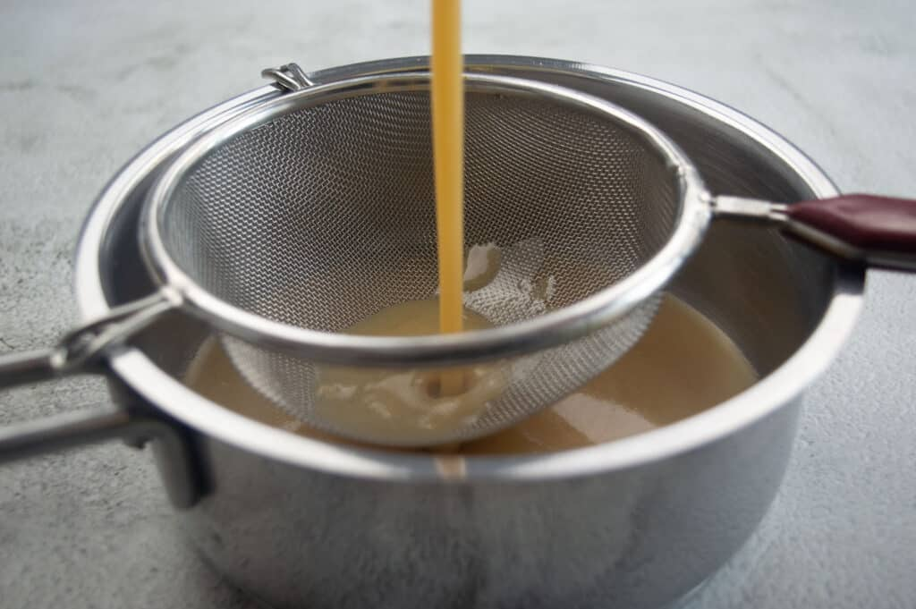 Sieving the sauce into another saucepan