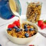 Vegan granola with a jug pouring soya milk