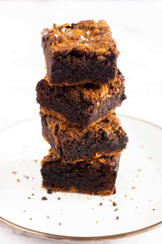 A stack of four gooey biscoff brownies with a sprinkle of flakey sea salt on top