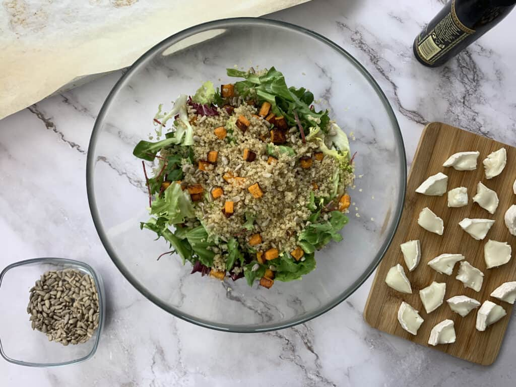 Adding butternut squash and quinoa to a bowl of mixed leafs