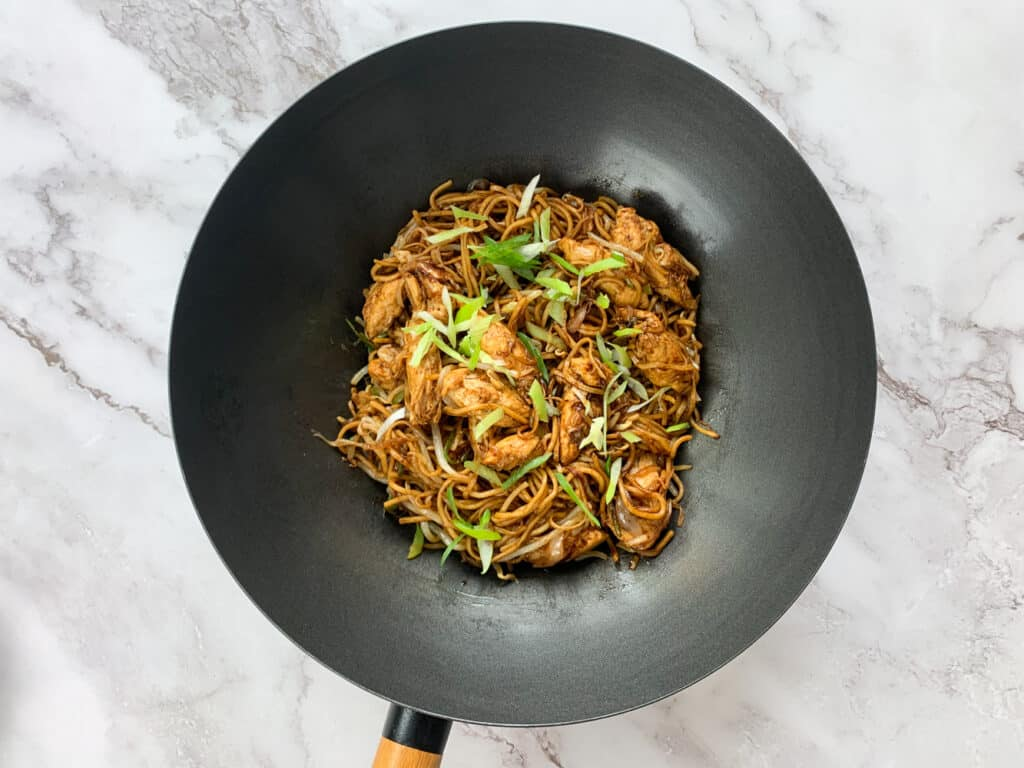 Finished Chow Mein in a large black wok, sprinkled with spring onions