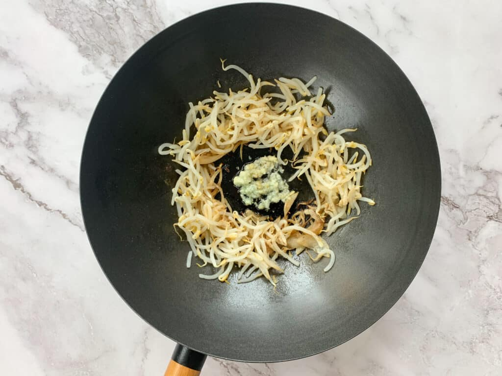 Adding bean sprouts and garlic to the wok