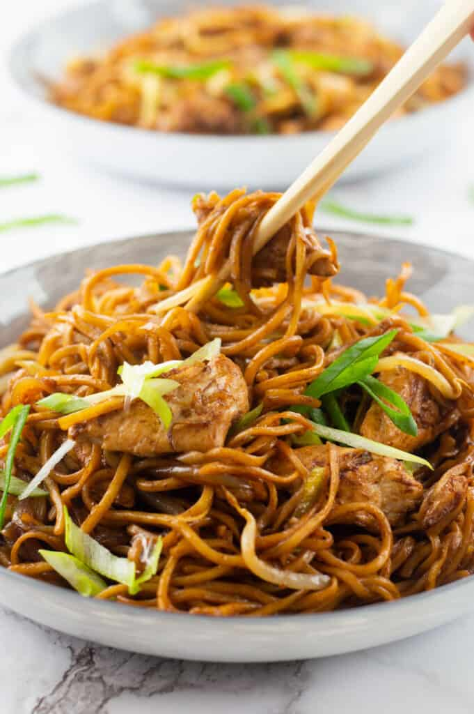 Two bowls of Chicken Chow Mein, with chop sticks grabbing a piece of chicken out of one
