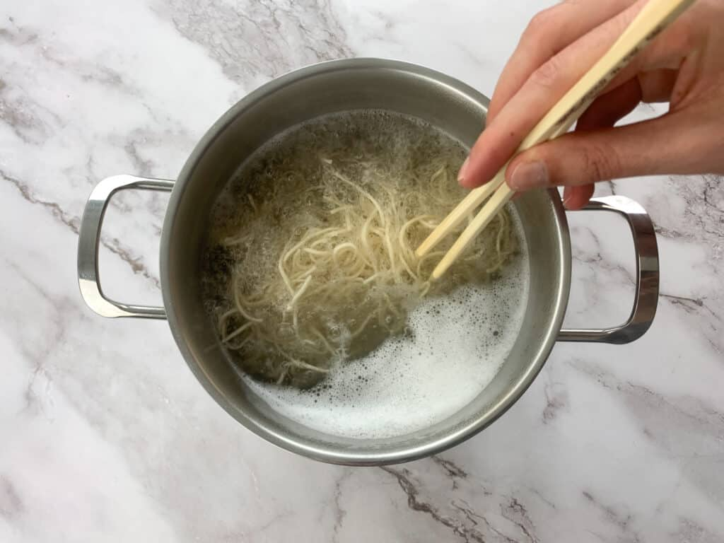 Mixing a large pot of cooking noodles