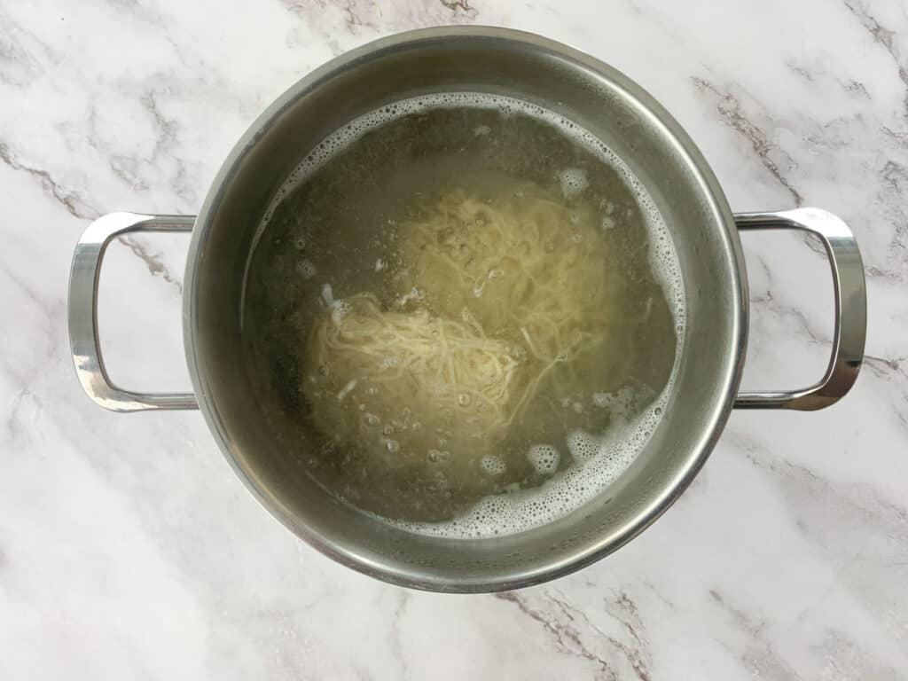 Large pot cooking dry wheat noodles