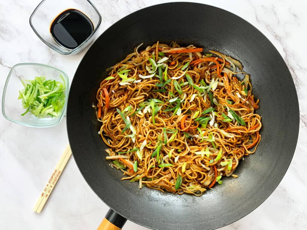 A wok full of vegetable chow mein with soy sauce and spring onions on the side