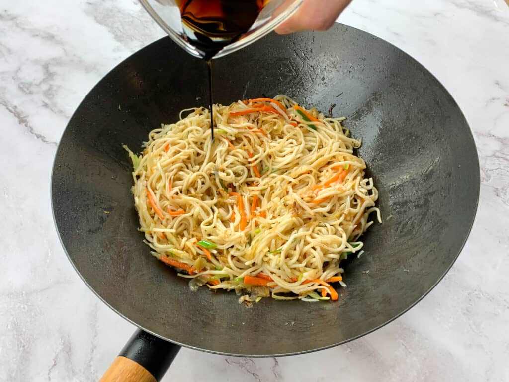 Adding soy sauce to the chow mein