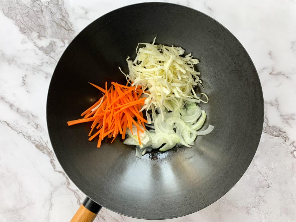 carrots, cabbage and onions in a large wok