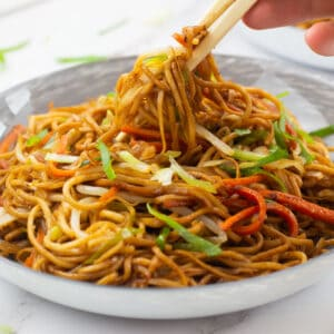Chop sticks picking up some noodles from a bowl of vegetable chow mein