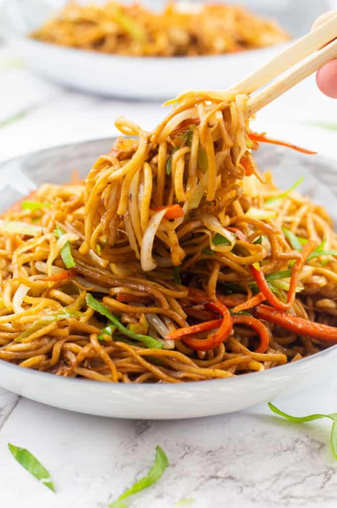 Chopsticks grabbing some noodles out of a bowl