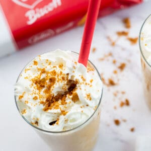 Biscoff milkshake in a tall glass and a red straw