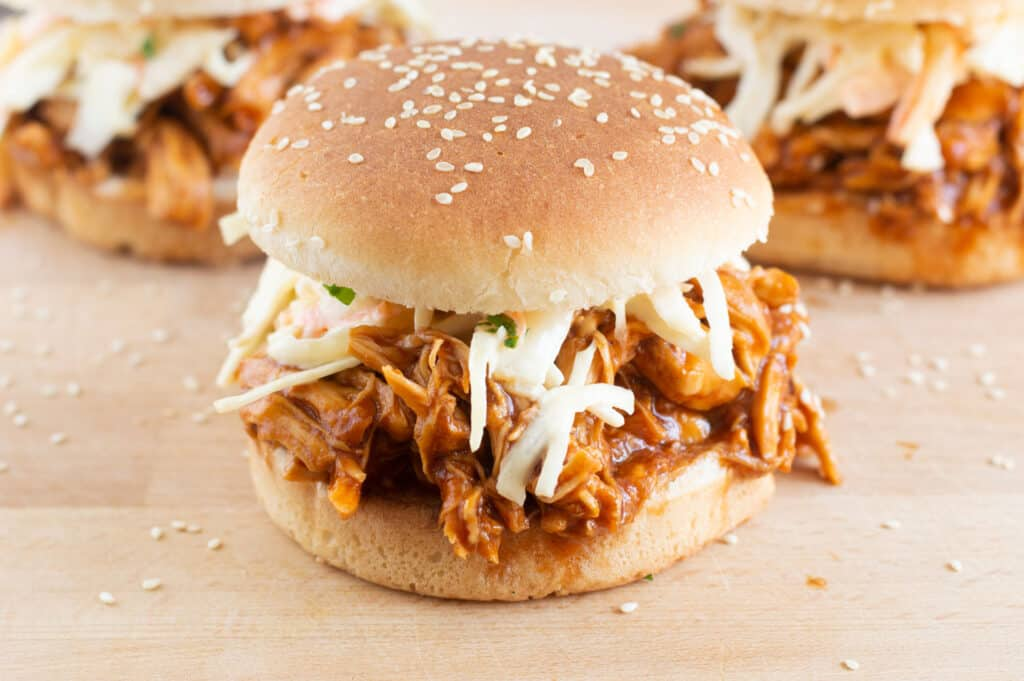 Crockpot cooked bbq chicken in a seeded burger bun with coleslaw