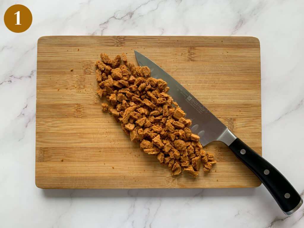 Biscoff biscuits roughly chopped on a wooden board