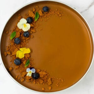 Biscoff Lotus cheesecake garnished with blueberries, biscuits, edible flowers and mint