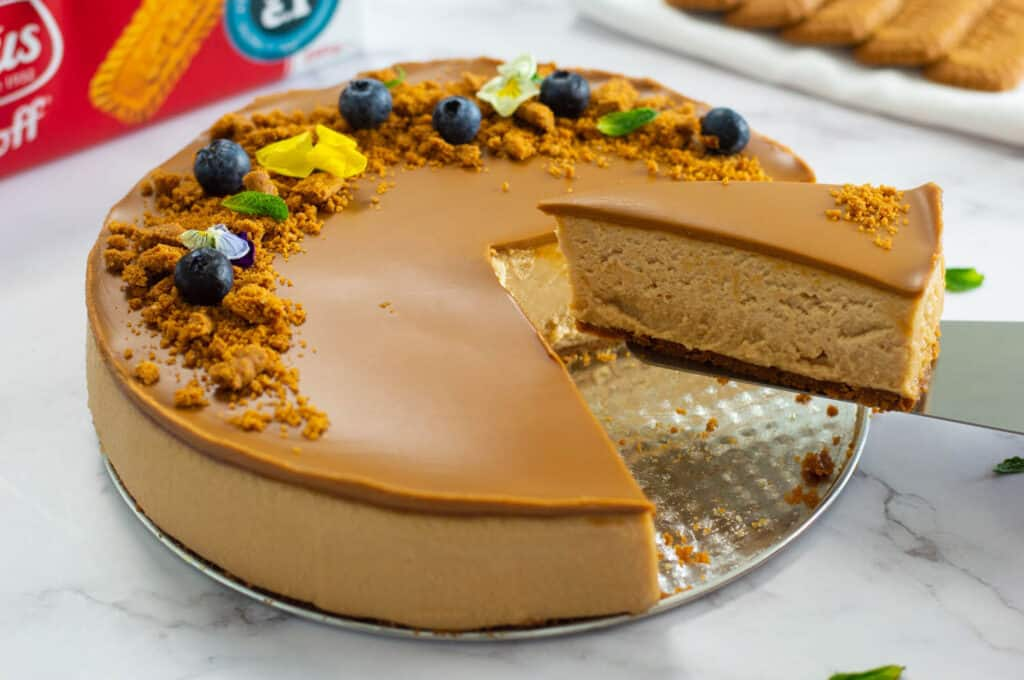 Biscoff cheesecake with a piece being lift out by a cake server