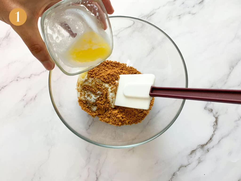 Melting butter being poured into a large bowl of Biscoff biscuits