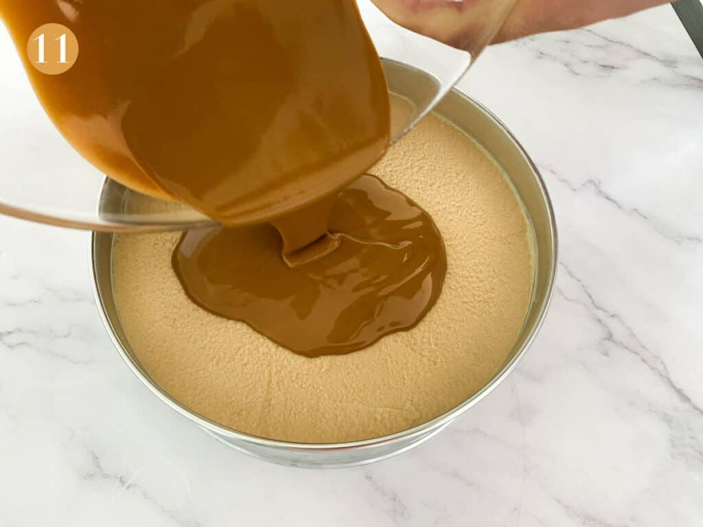Pouring melted biscoff spread onto a cheesecake
