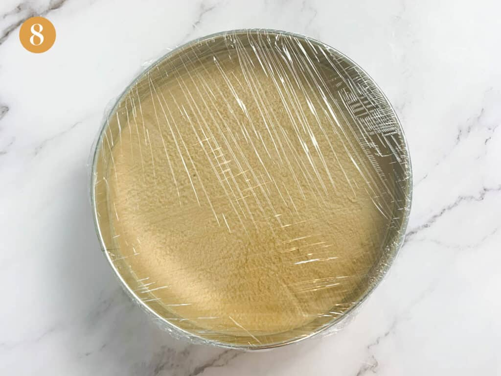 Heavily wrapped tight cling film over a cake tin