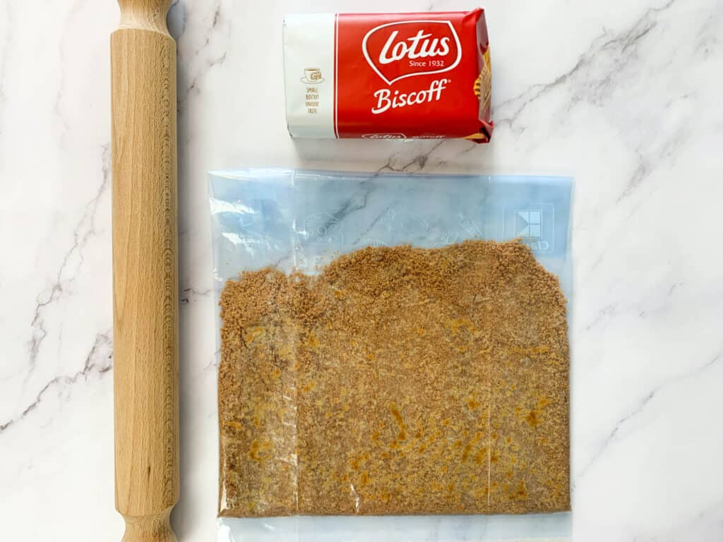 Biscoff biscuits finely crushed in a freezer bag with a rolling pin