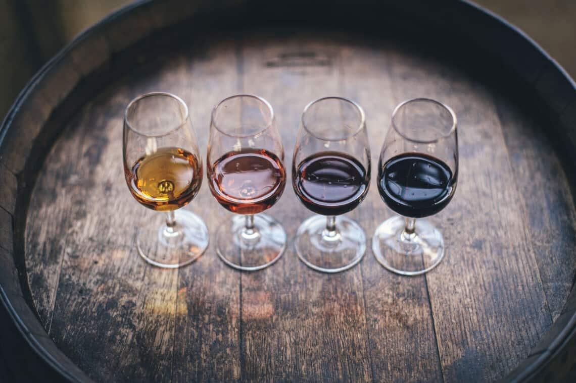Red wine vinegar, red wine, sherry vinegar and white wine vinegar in glasses on a oak barrel
