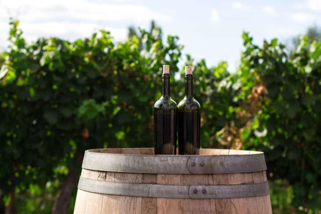 Sherry vinegar in glass bottles on a wooden barrel